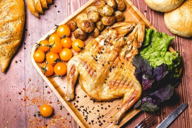 Vista superior pollo al tabaco frito con papas al horno y tomates ceri amarillos con hojas de ensalada en un tablero