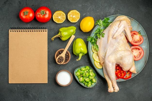 Vista superior de pollo crudo fresco con tomates, limón y verduras sobre un fondo oscuro