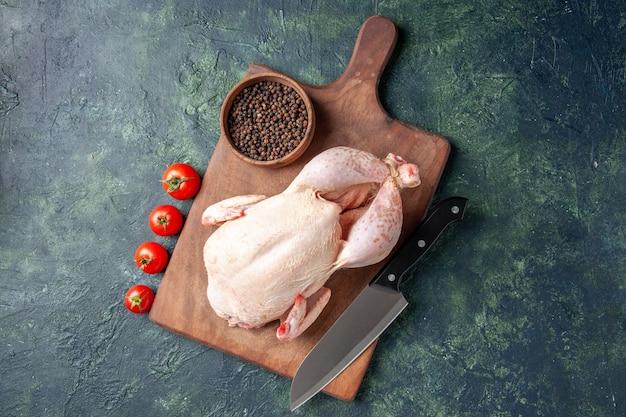 Vista superior pollo crudo fresco con tomates rojos sobre fondo azul oscuro comida de cocina foto de animales comida carne de pollo granja de color