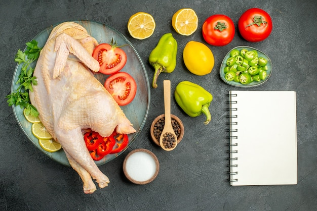 Vista superior de pollo crudo fresco con verduras de limón y verduras en el fondo oscuro