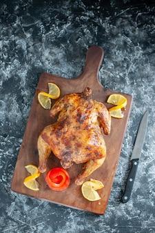 Vista superior de pollo con especias cocidas con limón sobre superficie gris claro