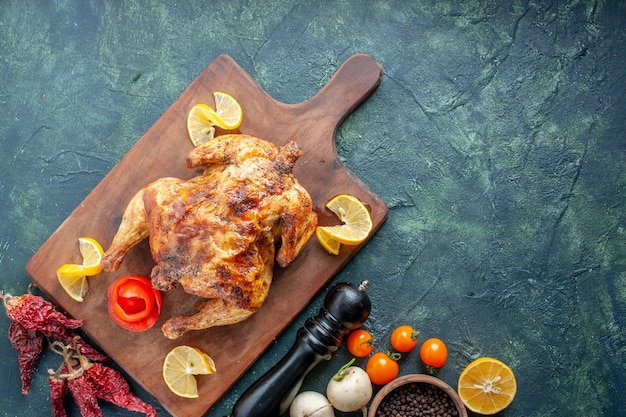 Vista superior de pollo con especias cocidas con rodajas de limón sobre una superficie oscura
