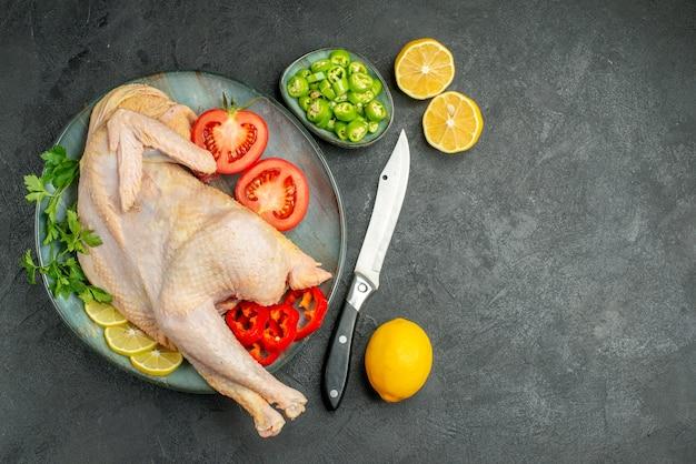 Vista superior de pollo fresco crudo dentro de la placa con verduras y verduras sobre fondo oscuro