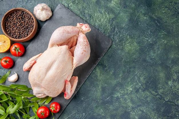 Vista superior de pollo fresco con tomates rojos sobre superficie azul oscuro