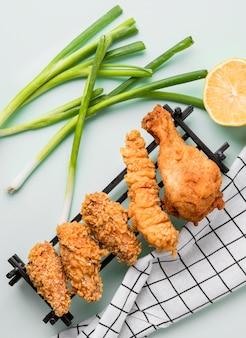 Vista superior de pollo frito en bandeja con cebolla verde, limón y toalla de cocina