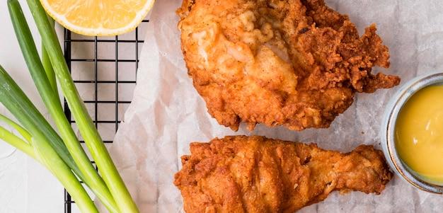 Vista superior de pollo frito con cebolla verde y salsa