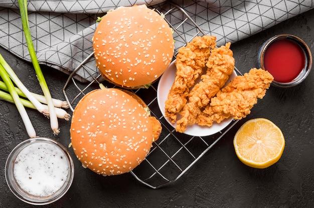 Vista superior de pollo frito y hamburguesas en bandeja con salsas
