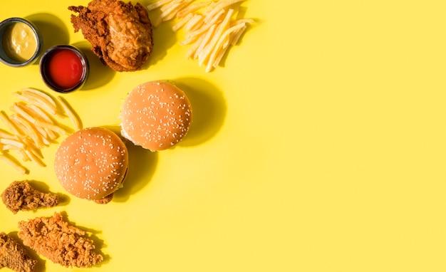 Vista superior de pollo frito, hamburguesas y papas fritas con espacio de copia