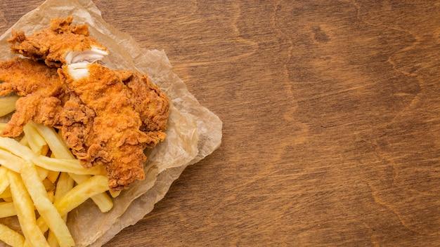 Vista superior de pollo frito y papas fritas con espacio de copia