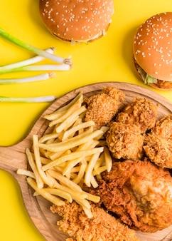 Vista superior de pollo frito y papas fritas con hamburguesas y cebollas verdes