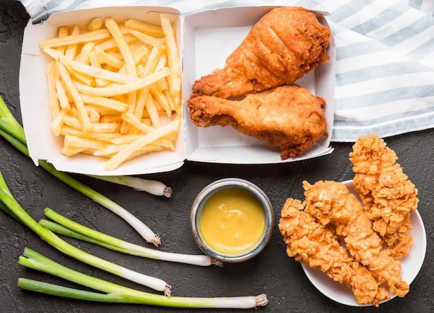 Vista superior de pollo frito y papas fritas con salsa
