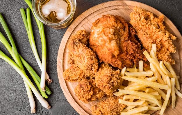 Vista superior de pollo frito con papas fritas en tabla de cortar y cebollas verdes