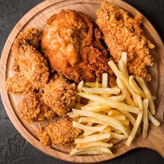 Vista superior de pollo frito con papas fritas en tabla de cortar