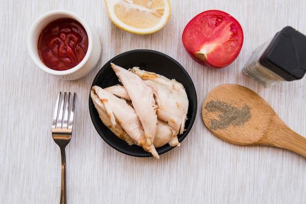 Vista superior de pollo hervido en plato negro con pimienta negra en polvo; tomate; limón; tenedor y salsa de tomate sobre escritorio de madera