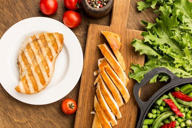 Vista superior de pollo a la plancha y tomates con ensalada
