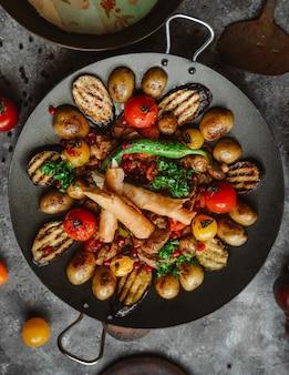 Vista superior de pollo saj con pimiento, berenjena, tomates, papas y pan plano