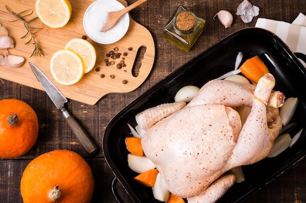 Vista superior de pollo en sartén con rodajas de limón para acción de gracias