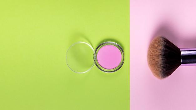 Vista superior de polvo y pincel sobre fondo rosa y verde