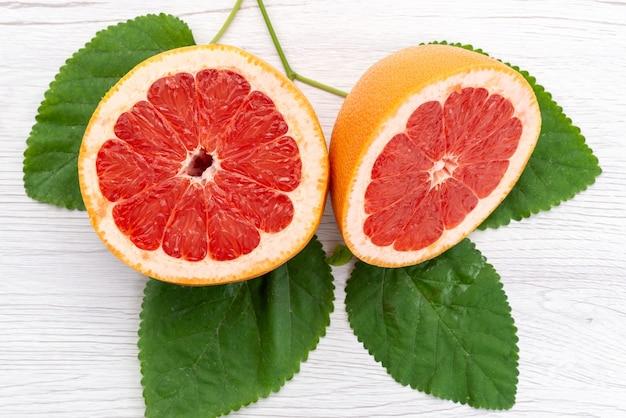 Una vista superior de pomelo fresco en rodajas suave y jugoso junto con hojas verdes sobre blanco, color de jugo de frutas cítricas