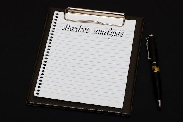 Vista superior del portapapeles y hoja en blanco escrita con análisis de mercado sobre fondo negro. concepto de negocio.
