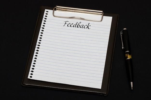 Vista superior del portapapeles y hoja en blanco escrita con comentarios sobre fondo negro. concepto de negocio.