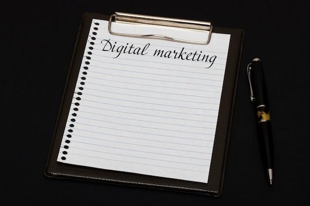 Vista superior del portapapeles y hoja en blanco escrita con marketing digital sobre fondo negro. concepto de negocio.
