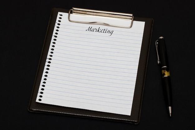 Vista superior del portapapeles y hoja en blanco escrita con marketing sobre fondo negro. concepto de negocio.