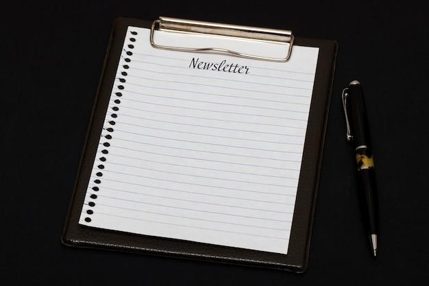 Vista superior del portapapeles y hoja en blanco escrita con newsletter sobre fondo negro. concepto de negocio.