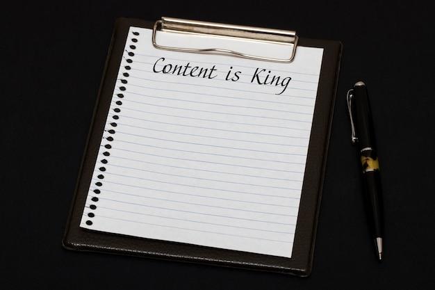 Vista superior del portapapeles y hoja en blanco escrita con ã â¡ontent es king sobre fondo negro. concepto de negocio.