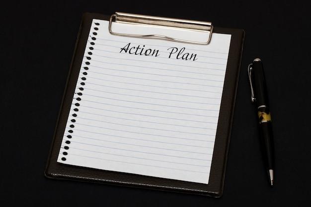 Vista superior del portapapeles y hoja en blanco escrita con plan de acción sobre fondo negro. concepto de negocio.