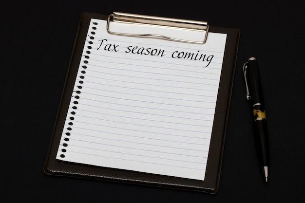 Vista superior del portapapeles y hoja en blanco escrita con temporada de impuestos sobre fondo negro. concepto de negocio.