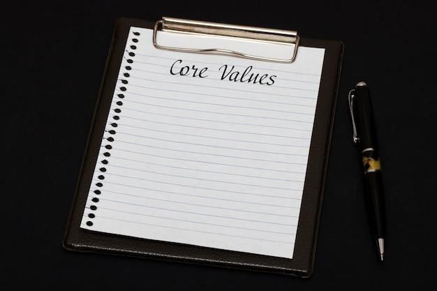 Vista superior del portapapeles y hoja en blanco escrita con valores fundamentales sobre fondo negro. concepto de negocio.
