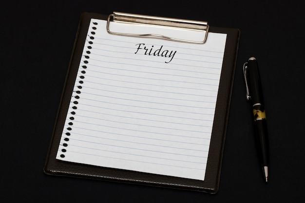 Vista superior del portapapeles y hoja en blanco escrita con viernes sobre fondo negro. concepto de negocio.