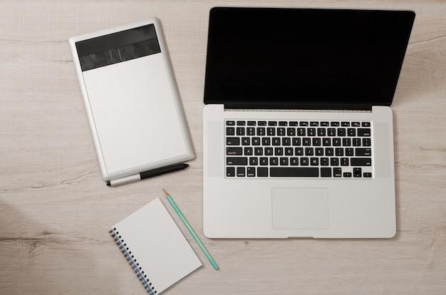 Vista superior del portátil abierto, tableta gráfica y cuaderno sobre una mesa de madera