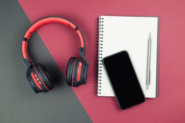 Vista superior del portátil con bolígrafo, teléfono inteligente y auriculares