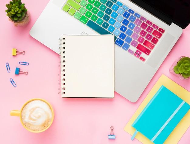 Vista superior del portátil con cuaderno en blanco