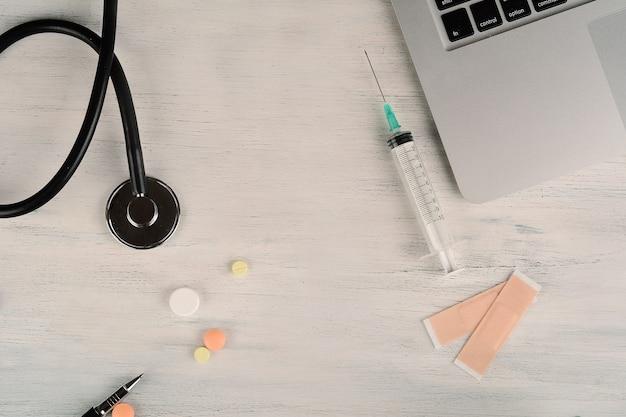 Vista superior de portátil, estetoscopio y pastillas.