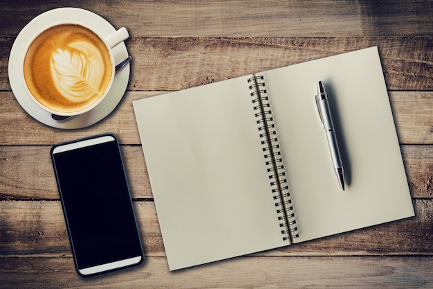 Vista superior portátil, lápiz, taza de café y teléfono en la mesa de madera, vintage filtro.