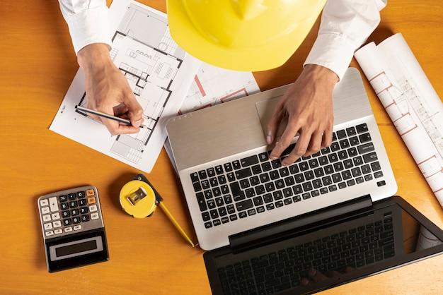 Vista superior del portátil y materiales de papelería en el escritorio