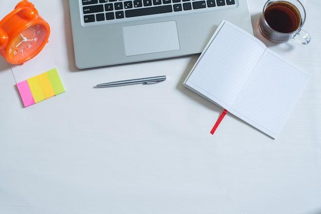 Vista superior del portátil, taza de té, cuaderno abierto, bolígrafo, mini papel colorido, reloj naranja