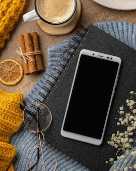 Vista superior del portátil y teléfono inteligente en suéter con taza de café