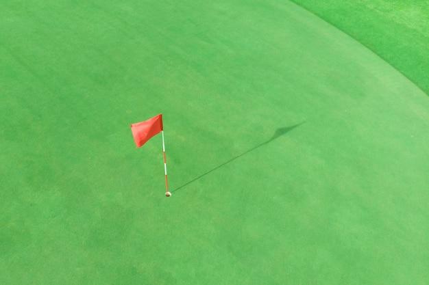 Vista superior del poste de golf en el green en un campo de golf con copyspace en blanco