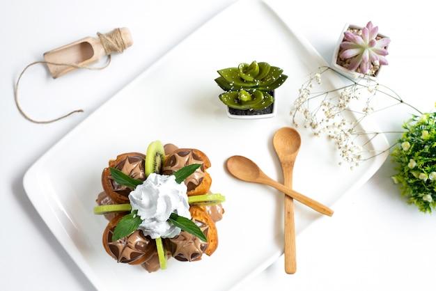 Una vista superior de postre choco con kiwis en rodajas y crema pastelera dentro de un escritorio blanco junto con cucharas de madera y plantas en la mesa blanca, fruta exótica dulce
