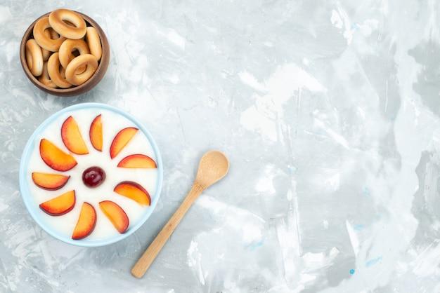 Vista superior postre con frutas en rodajas frutas dentro de la placa junto con galletas dulces en blanco