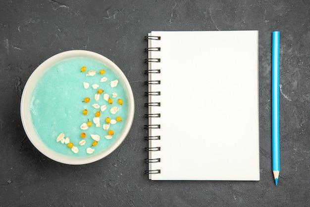 Vista superior de postre helado azul dentro de la placa en el piso oscuro color helado crema