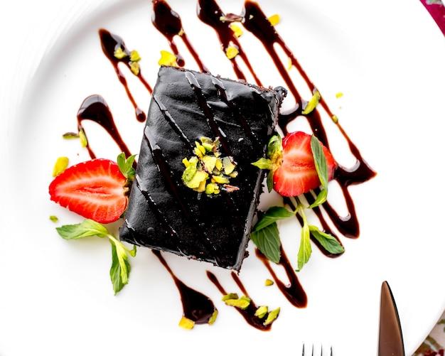 Vista superior postre pastel de chocolate con rodajas de fresa y glaseado de chocolate