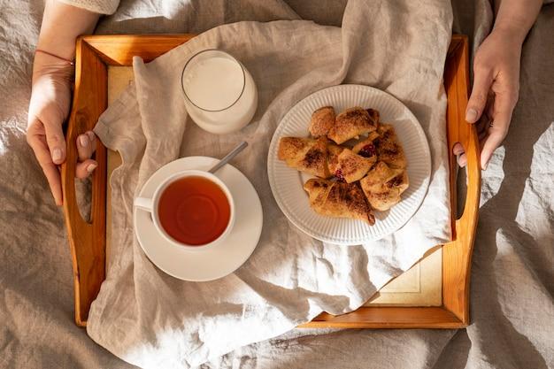 Vista superior de postres en bandeja con té y leche