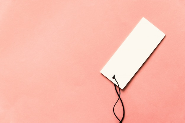 Vista superior del precio blanco vacío con cuerda negra sobre fondo rosa. fondo con espacio de copia.