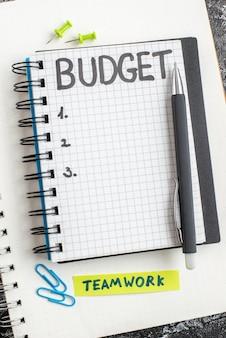 Vista superior del presupuesto nota escrita en el bloc de notas con bolígrafo sobre la superficie oscura cuaderno de color gris dinero gris de la universidad