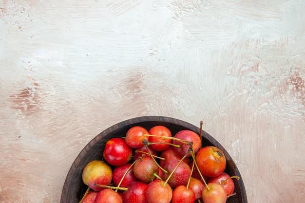 Vista superior de primer plano cerezas tazón de cerezas rojo-amarillo sobre la mesa